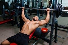 一间健身房的热的肌肉人在使用杠铃的卧推,在被弄脏的黑暗的背景的锻炼设备 库存照片