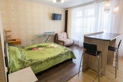 一间卧室的内部有一个沙发的在一室公寓 免版税库存图片