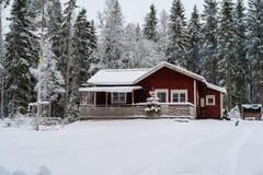 一间小的红色客舱在雪盖的森林里 免版税库存照片