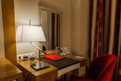 一间屋子在旅馆是一个工作场所在旅馆里,并且在书桌有文件夹,有电话 库存照片