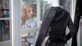 一间时髦的礼服rassatrivaet陈列室的一个少妇与一件皮革背心,她在精品店要买 股票视频