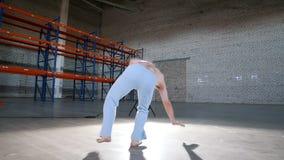 一间明亮的屋子 训练他的capoeira技能和执行轻碰的一个运动人 影视素材