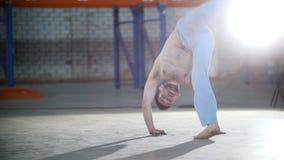 一间明亮的屋子 训练他的capoeira技能和跳跃在他的手上的一个运动赤裸上身的人 股票录像