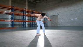 一间明亮的屋子 训练他的capoeira技能的一个运动人 股票视频