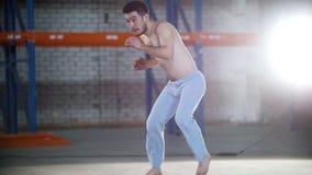 一间明亮的屋子 训练他的capoeira技能的一个运动赤裸上身的人 影视素材