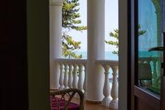 一间高级旅馆屋子的阳台有白色专栏的与一把软的舒适的椅子有海的美丽的景色 免版税库存照片