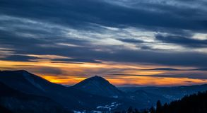 一非常有趣的日落 看法从上面在距离的小山 天空的蓝色和黄色颜色在背景中 免版税库存图片