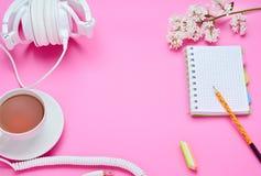 一面少年儿童,铅笔笔记本橡皮擦花饮料玻璃的构成的桌的顶视图与耳机的在桃红色 库存照片