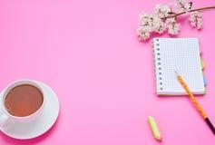 一面少年儿童,铅笔笔记本花的构成的桌的顶视图每杯在桃红色背景的饮料 免版税库存照片