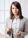 一面英俊的女实业家有柄小镜的纵向 免版税库存图片