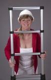 戴一顶安全帽和拿着一架望远镜梯子的妇女 免版税库存图片