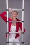 戴一顶安全帽和拿着一架望远镜梯子的妇女 免版税库存照片