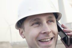一顶安全帽的年轻微笑的男性工程师在风轮机旁边的电话,特写镜头 免版税库存照片