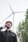 一顶安全帽的年轻微笑的男性工程师在风轮机旁边的电话 图库摄影