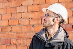 一顶工程师佩带的安全帽的画象在工地工作的 库存图片