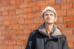 一顶工程师佩带的安全帽的画象在工地工作的 图库摄影