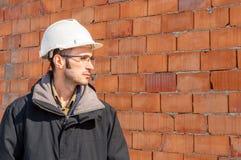一顶工程师佩带的安全帽的画象在工地工作的 免版税库存图片