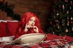 一顶红色假发的一个十几岁的女孩在床上在圣诞节的一间屋子里 时尚,新年 免版税库存照片