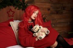 一顶红色假发的一个十几岁的女孩在床上在圣诞节的一间屋子里 时尚,新年 库存图片