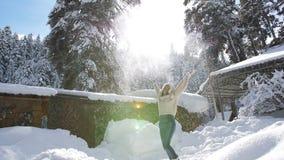 一顶被编织的毛线衣和裘皮帽的美女在瑞士山中的牧人小屋附近享受一个晴朗的冬日 股票视频