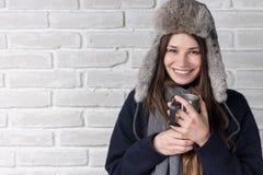 一顶裘皮帽的女孩有温暖的饮料的 库存图片