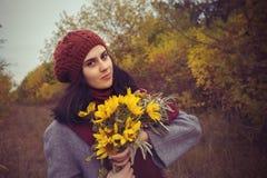 一顶贝雷帽的微笑的女孩在秋天森林里 库存图片