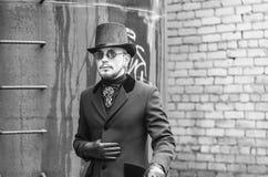 一顶黑外套和高顶丝质礼帽的在19世纪的贫民窟,蒸汽废物年轻人 免版税图库摄影