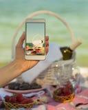 一顿夏天野餐的照片在海滩的在智能手机 库存图片