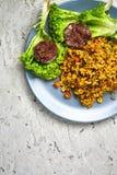 一顿意大利煨饭的顶视图与菜和素食主义者甜菜炸肉排的在一个灰色具体背景的一个蓝色盘服务 库存照片