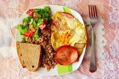 一顿晚餐的盘从煮沸的荞麦香肠煎蛋和新鲜蔬菜 免版税图库摄影