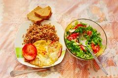 一顿晚餐的盘从煮沸的荞麦香肠煎蛋和新鲜蔬菜 免版税库存图片