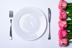 一顿浪漫晚餐的装饰:花和板材 免版税库存图片
