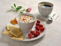 一顿自然光早餐在一张明亮的桌布供应 用玫瑰色花装饰 库存照片