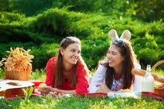 一顿野餐的两个美丽的女孩在夏天在谈的公园获得乐趣和拷贝空间 图库摄影