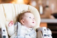 一顿高脚椅子等待的晚餐的甜女婴 免版税图库摄影