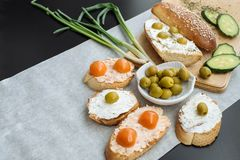 一颗有壳的长方形宝石切片的顶视图用西红柿、黄瓜和绿橄榄,乳脂干酪 免版税图库摄影