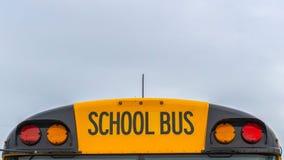 一黄色学校班车和多云天空的全景正面图有家的在背景中 免版税库存照片