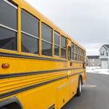一黄色学校班车的正方形外视图有一个红色停车牌和尽管信号灯的 免版税库存照片