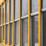 一黄色学校班车的正方形外视图有关闭的在玻璃窗 图库摄影