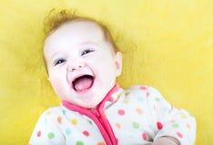 一件五颜六色的毛线衣的滑稽的笑的婴孩在黄色毯子 免版税库存图片