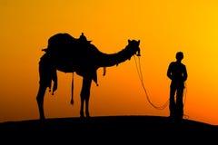 一头人和骆驼的剪影在日落在沙漠, Jaisalmer -印度 免版税库存图片