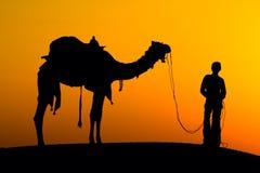 一头人和骆驼的剪影在日落在沙漠, Jaisalmer -印度 免版税库存照片