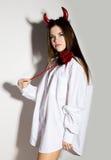 一件人` s白色衬衣的女孩有举行三叉戟和看起来俏丽的恶魔的红色垫铁的 免版税库存图片