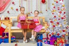 给一件伟大的礼物坐在圣诞节设置的一条长凳的愉快的女孩 免版税库存照片