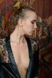 一件黑便服的年轻金发碧眼的女人 免版税库存图片
