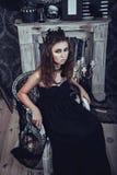 一件典雅的黑礼服的哥特式少妇在扶手椅子 图库摄影