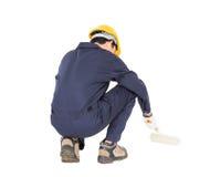 一件制服的工作者使用漆滚筒绘无形的f 免版税库存图片
