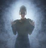一件吸血鬼礼服的一个少妇在有雾的背景 免版税库存照片