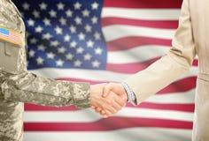 一致和民用人的美国军人衣服的与在背景-美国的国旗握手 免版税图库摄影