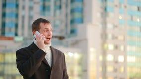 一件外套的人有一个电话的在摩天大楼背景的一个现代城市  影视素材